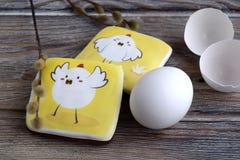 Les pains d'épice avec des images des poulets, de l'oeuf et d'une coquille d'oeufs sont sur une table en bois photo libre de droits