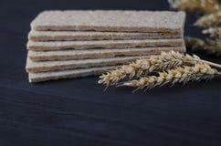 Les pains diététiques d'air se trouvent sur une table en bois sur un fond foncé à côté des oreilles du blé photos libres de droits