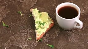 Les pains grillés avec le pâté d'avocat, frais microgreen et mettent en forme de tasse du café sur le fond concret foncé clips vidéos