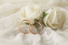 Les paires d'anneaux de mariage d'or au-dessus d'invitation cardent décoré de la dentelle photos stock