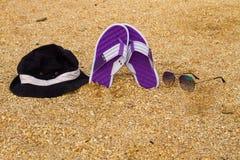 Les paires de bascules électroniques, de chapeau et de lunettes de soleil sur une mer arénacée échouent Photographie stock libre de droits