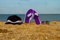 Les paires de bascules électroniques, de chapeau et de lunettes de soleil sur une mer arénacée échouent Photo libre de droits