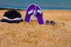 Les paires de bascules électroniques, de chapeau et de lunettes de soleil sur une mer arénacée échouent Image stock