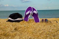Les paires de bascules électroniques, de chapeau et de lunettes de soleil sur une mer arénacée échouent Photo stock