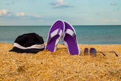 Les paires de bascules électroniques, de chapeau et de lunettes de soleil sur une mer arénacée échouent Image libre de droits