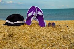 Les paires de bascules électroniques, de chapeau et de lunettes de soleil sur une mer arénacée échouent Photographie stock