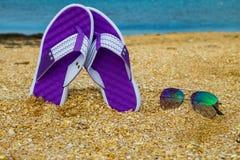 Les paires de bascules électroniques et de lunettes de soleil sur une mer arénacée échouent Photo stock