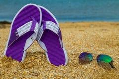 Les paires de bascules électroniques et de lunettes de soleil sur une mer arénacée échouent Images stock