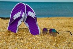 Les paires de bascules électroniques et de lunettes de soleil sur une mer arénacée échouent Photos stock