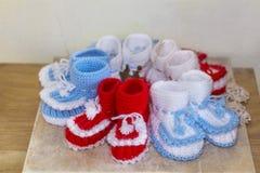 Les paires de blanc fait main et de rouge ont tricoté des pantoufles Photos stock