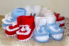 Les paires de blanc fait main et de rouge ont tricoté des pantoufles Photos libres de droits