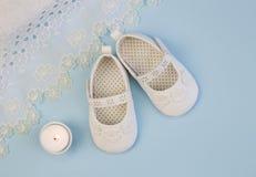 Les paires de butins blancs de bébé sur le fond bleu avec la dentelle baptisent Photographie stock