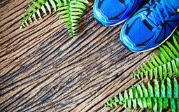 Les paires de chaussures de course bleues se sont étendues sur un backgro en bois grunge de plancher Photo libre de droits