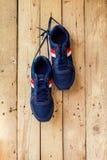 Les paires de chaussures de sport accrochent sur un clou sur le mur en bois Photo stock