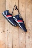 Les paires de chaussures de sport accrochent sur un clou sur le mur en bois Photographie stock libre de droits