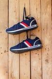 Les paires de chaussures de sport accrochent sur un clou sur le mur en bois Images stock