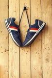 Les paires de chaussures de sport accrochent sur un clou sur le mur en bois Photos libres de droits