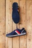 Les paires de chaussures de sport accrochent sur un clou sur le mur en bois Photos stock