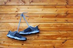 Les paires de chaussures de sport accrochent sur un clou sur un mur en bois brun Photos stock