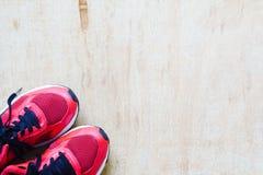 Les paires de chaussures rouges de sport se sont étendues sur le fond en bois grunge de plancher, Images stock