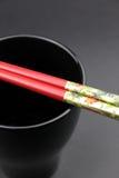 Les paires de Chinois coupent des bâtons sur une cuvette noire Photographie stock
