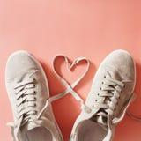 Les paires de coureurs gris avec des dentelles faisant un coeur forment Photos stock