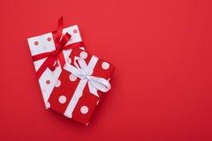 Les paires de deux ont pointillé des boîte-cadeau sur le fond rouge Image stock