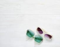 Les paires de ` s de dames âgées et de ` s d'hommes ont façonné des lunettes de soleil sur le fond blanc en bois de plancher photographie stock