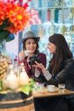 Les paires de touristes d'amis s'asseyant à une barre ajournent observer les photos sur le moniteur SLR Photographie stock