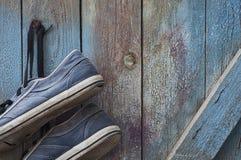 Les paires de vieilles espadrilles bleues sales et usées accrochent sur un clou Photographie stock