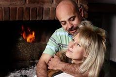 Les paires heureuses s'approchent d'une cheminée Images libres de droits