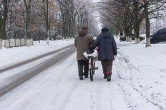 Les paires pluses âgé marchant sur une rue d'hiver roulant la vieille bicyclette ont chargé avec des sacs dans la ville de Dniepr Images stock