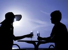 Les paires silhouettent se reposent à une table et retiennent des gobelets Image libre de droits