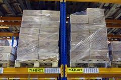Les palettes avec des boîtes se tiennent sur un entrepôt de marchandises d'étagère Image libre de droits