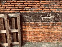 Les palettes en bois se sont inclinées devant le mur de briques rouge photos libres de droits