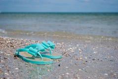 Les pantoufles en bon état vertes d'espadrilles sur le bord de la mer arrosent l'été de ciel bleu Photos stock