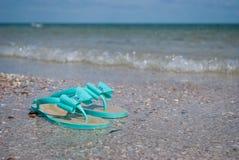 Les pantoufles en bon état vertes d'espadrilles sur le bord de la mer arrosent l'été de ciel bleu Image libre de droits