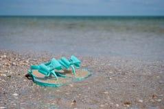 Les pantoufles en bon état vertes d'espadrilles sur le bord de la mer arrosent l'été de ciel bleu Photographie stock