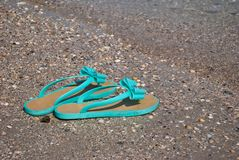 Les pantoufles en bon état vertes d'espadrilles sur le bord de la mer arrosent l'été de ciel bleu Photo libre de droits