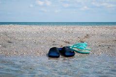 Les pantoufles masculines et femelles d'espadrilles sur le bord de la mer arrosent l'été de ciel bleu Photo stock