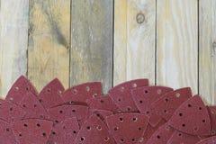 Les papiers de sable de triangle sur les conseils en bois ont placé le fond Photos stock