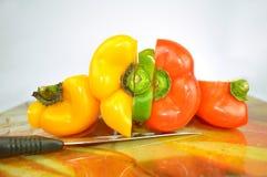 Les paprikas - jaune, vert et rouge - ont coupé dans les morceaux Photographie stock libre de droits