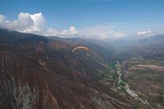 Les parapentistes rouges volent le long du flanc de montagne au-dessus de River Valley sous un ciel bleu avec les cumulus blancs Image libre de droits