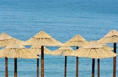 Les parapluies de paille sur la plage avec la turquoise arrosent Photographie stock libre de droits