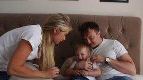 Les parents affectueux jouent avec leur fils sur le lit riant et souriant dans la chambre à coucher banque de vidéos