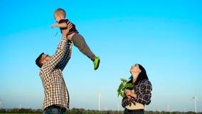 Les parents aimants jouent avec leur enfant dans un domaine Le père jette le garçon en l'air tandis que la mère les regarde avec  banque de vidéos
