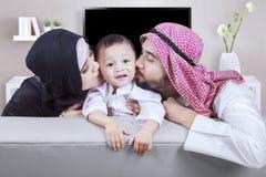 Les parents Arabes embrassent leur fils à la maison Image libre de droits