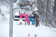 Les parents avec des enfants dans le ski président le levage vers le haut du terra de ski Photographie stock libre de droits