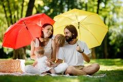 Les parents de brunes avec deux enfants ont un repos sur la pelouse sous les parapluies rouges et jaunes lumineux les couvrant du photo libre de droits