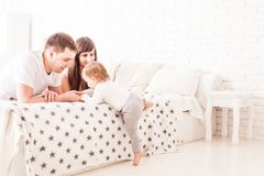 Les parents enseignent l'enfant à s'élever sur le lit Photographie stock libre de droits